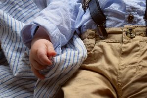 Baby with blanket, wearing trousers, braces