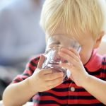toddler drinking water from a glass