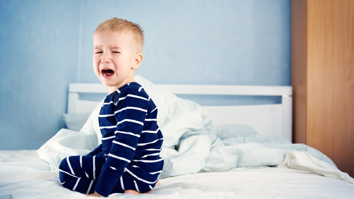 toddler crying in a bed