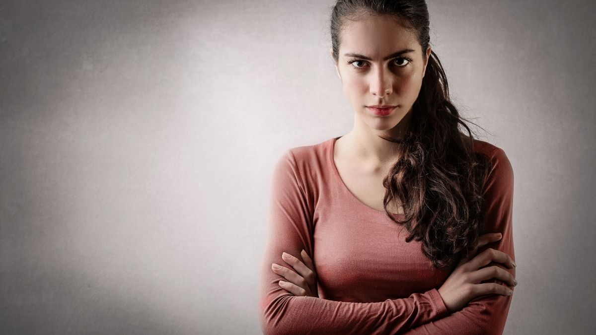 annoyed woman staring at camera with arms crossed