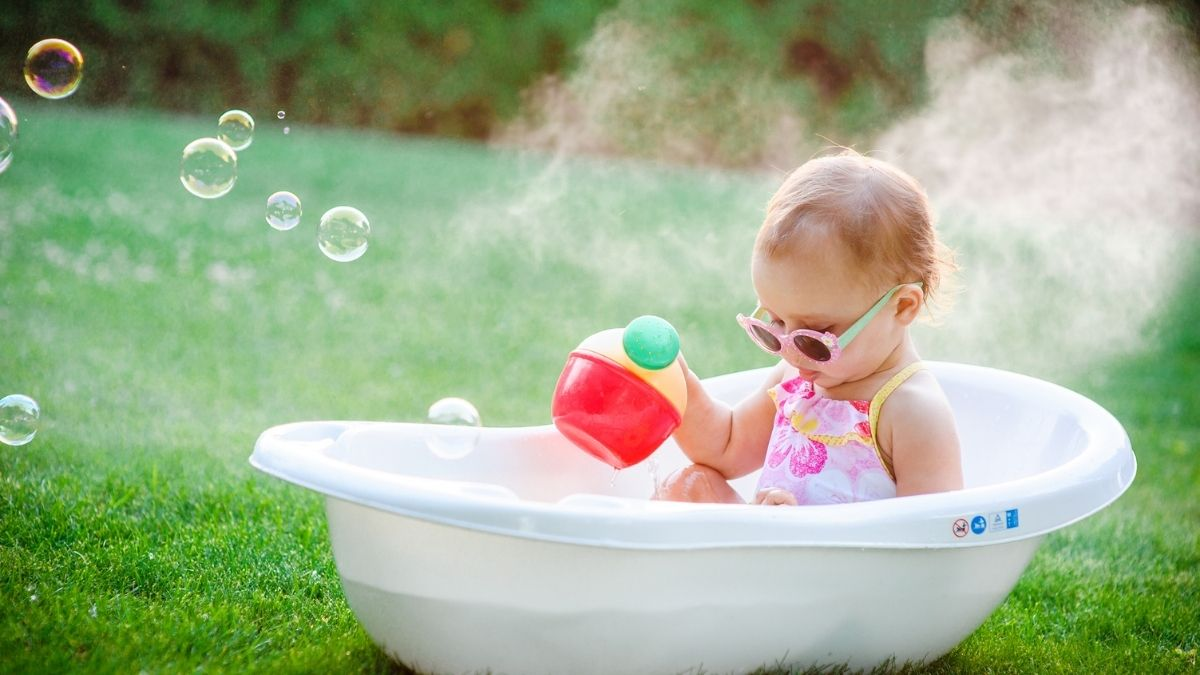 baby wearing sunglasses in bath outside with watering can