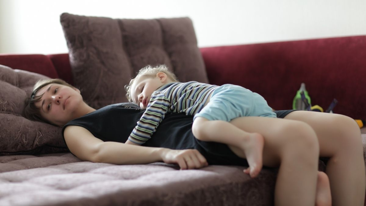 mom laying awake with toddler sleeping on her stomach