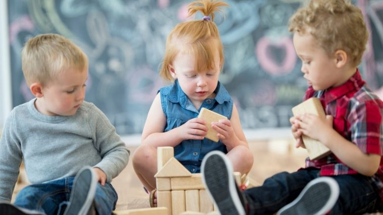 3 kids sharing a wooden building toy