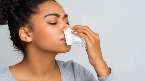 lady with tissue under nose catching nose bleed