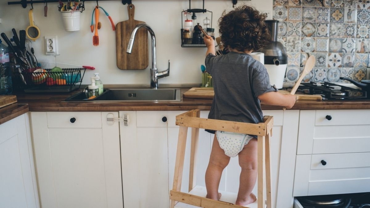toddler standing on learning tower in kitchen