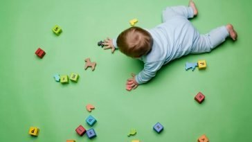baby crawling on green floor