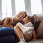 mom and grateful child on sofa with dog