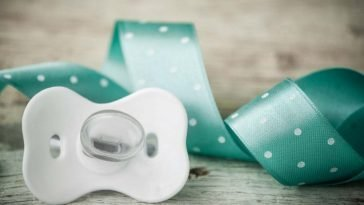 white pacifier with a green ribbon