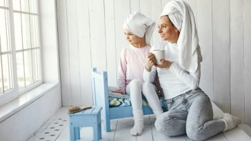 mom and daughter sitting on bed with towels on their heads relaxing