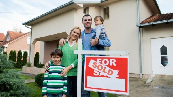 family proudly standing outside their new house