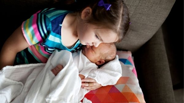 sibling with baby on couch