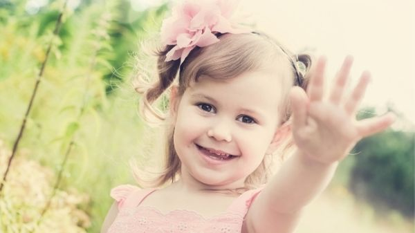 happy 3 year old giving high five to camera