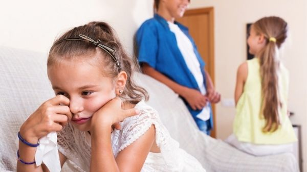 girl jealous of her old siblings crying on sofa