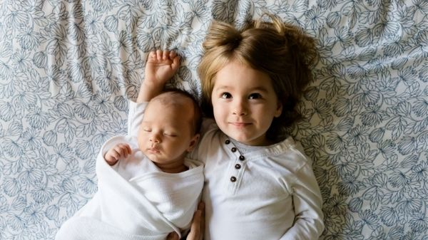 toddler and baby laying on bed