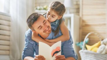 dad reading a book to his daughter