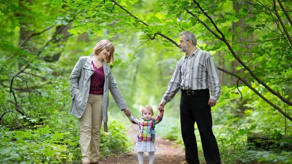 young grandparents walking granddaughter in woodland