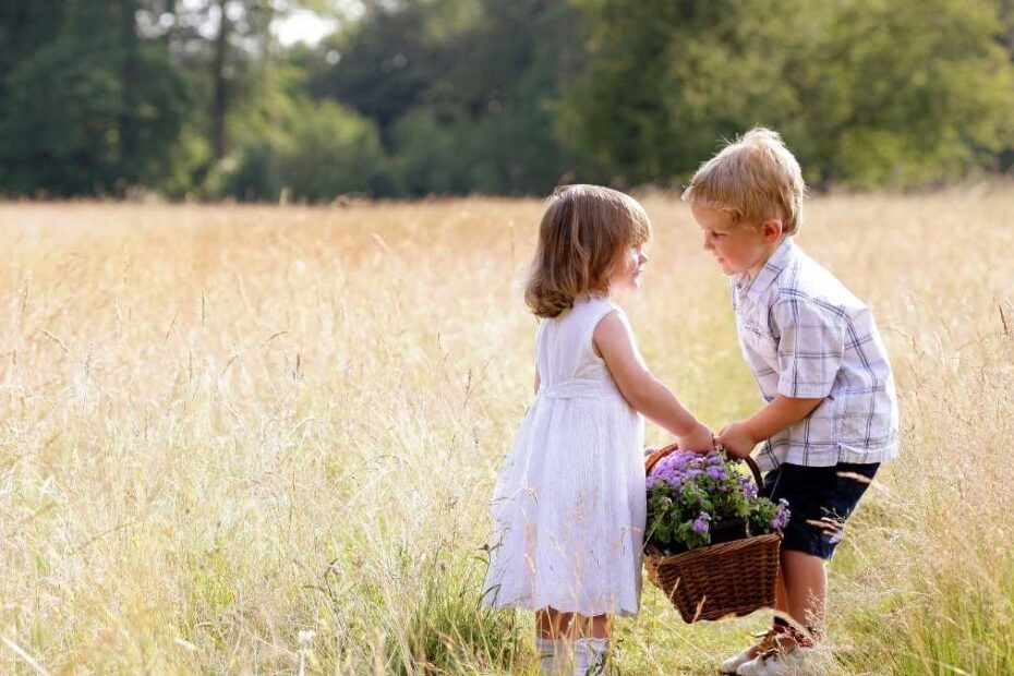boy helping girl carry a basket of flowers being kind