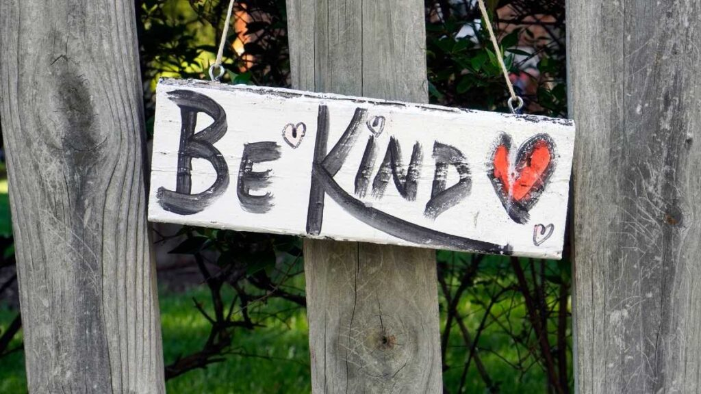 garden sign says be kind with red heart