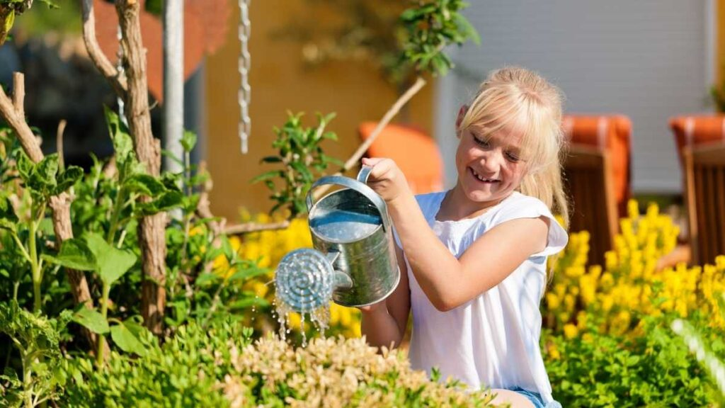 girl helping by watering plants