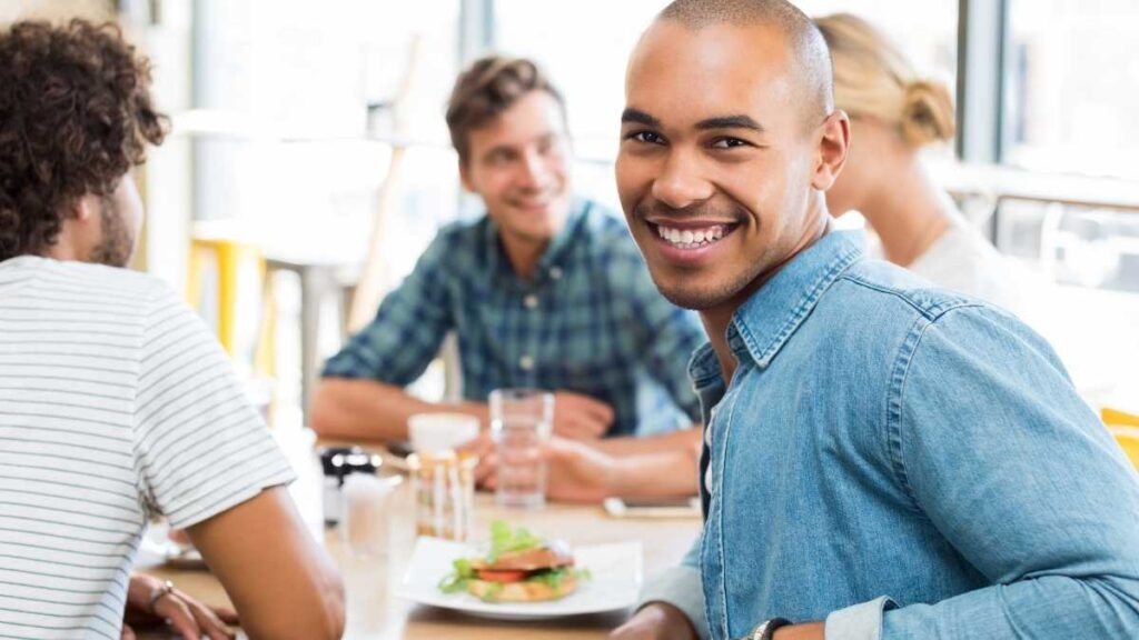 man out with friends socializing at a table eating lunch