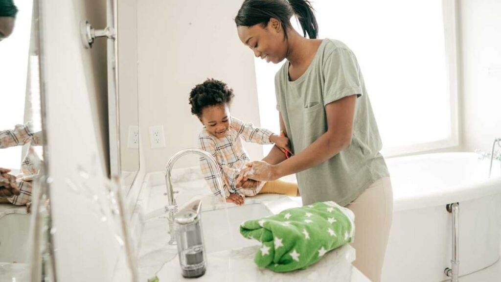 mom washing hands with toddler