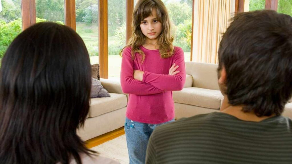 girl standing in front of parents with arms crossed