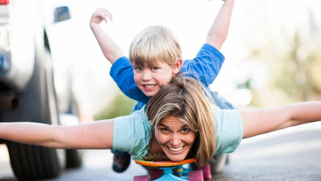 mom playing with her boy on skateboard