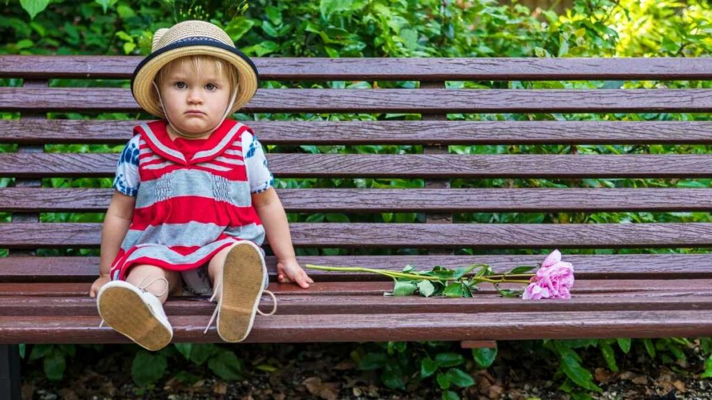toddler looking sad on bench with flower